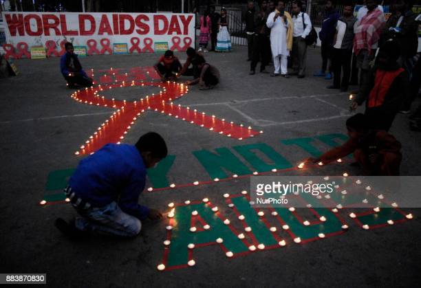Social activists and street children lighting the lamp on a red ribbon symbol on the eve of World AIDS Day on the banks of the River Ganges in...