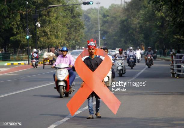 Social activists holds awareness placards and AIDS red ribbon logo as they walk in a carnival on WOrld AIDs Day in the eastern Indian state Odisha's...