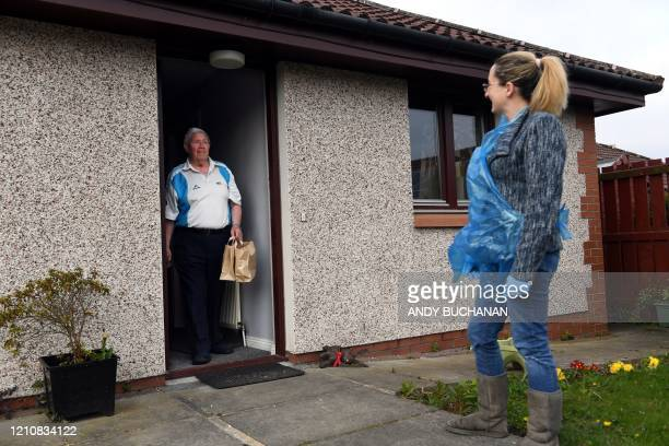 Social Bite social enterprise volunteer Stephanie Malone delivers free packed lunches to resident Alex Gibson in Edinburgh, Scotland on April 22...
