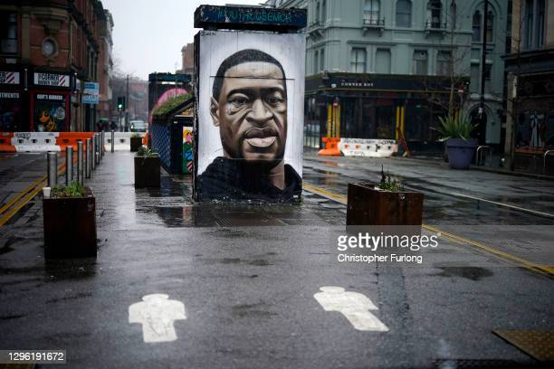 Social distance markers adorn the deserted pavement in front of a mural of George Floyd in Manchester during lockdown three on January 13, 2021 in...