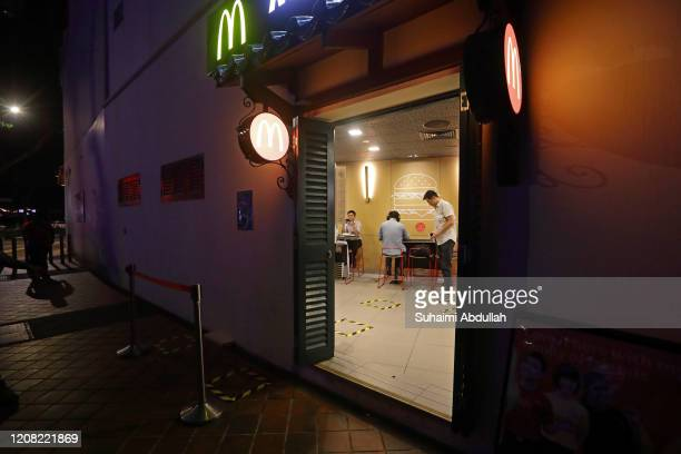 Social distance markers for queueing are seen at a McDonald's outlet on March 25 2020 in Singapore The Singapore government is set to close all...