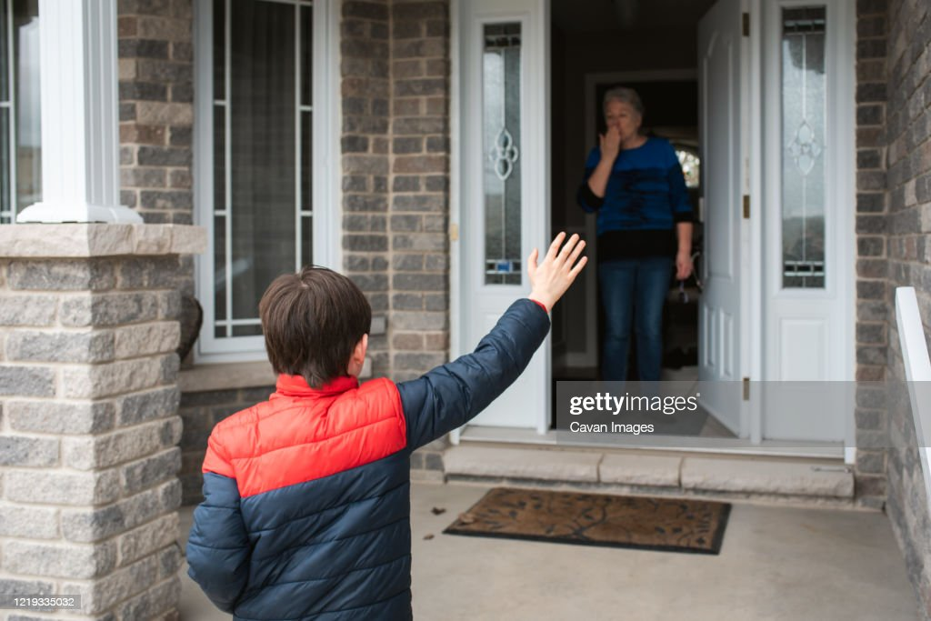 Social distance visit between young boy and his grandmother at home. : Stock Photo