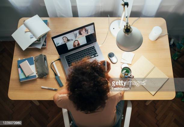 social distancing and self care: happy woman teleconferencing from home - adult stock pictures, royalty-free photos & images