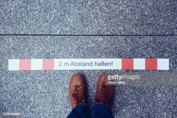 social distancing at store. shoes of an  unrecognizable person standing on distance sign waiting in line. - entfernt stock-fotos und bilder
