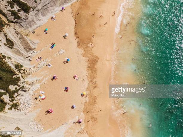 social distancing at the beach - summer 2020 - coronavirus - beach sunbathing spain stock pictures, royalty-free photos & images
