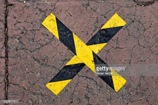 social distancing cross in yellow and black plastic sticky tape on a pavement outside a store - x marks the spot stock pictures, royalty-free photos & images