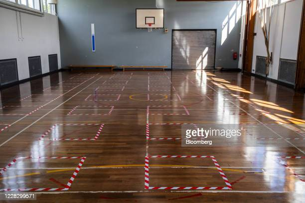 Social distancing floor markers sit near a basketball hoop in a gynasium at All Saints Catholic College ahead of reopening for students in...