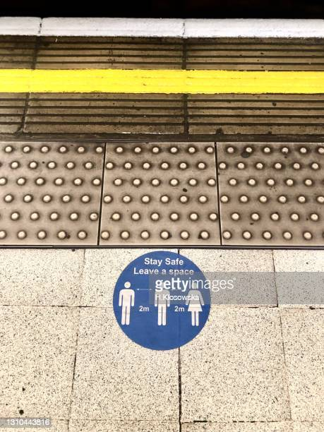 social distancing floor sticker on london underground platform - western script stock pictures, royalty-free photos & images