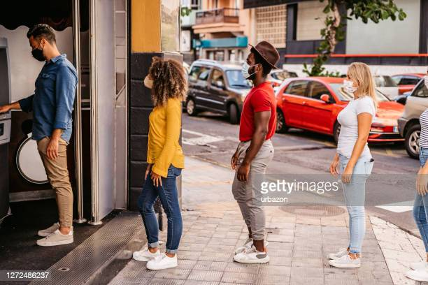 social distancing in line at atm - lining up stock pictures, royalty-free photos & images