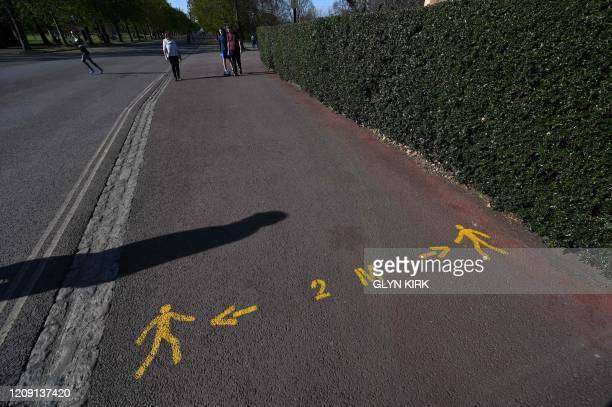 Social distancing is drawn on the pathway as people take their daily exercise in Greenwich Park in south London on April 4 as life continues in the...