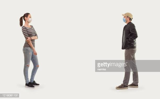 social distancing, man and woman standing with distance for avoid virus - distant stock pictures, royalty-free photos & images