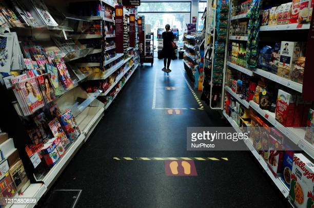 Social distancing markers subdivide the aisle space of a branch of supermarket chain Sainsbury's in the Bayswater district of London, England, on May...
