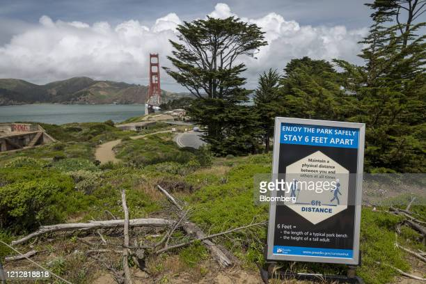 Social distancing sign is displayed in the Presidio near the Golden Gate Bridge in San Francisco, California, U.S., on Tuesday, May 12, 2020....