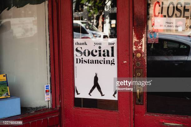 A social distancing sign is displayed outside a business in downtown Asheville North Carolina US on Wednesday July 15 2020 At least 93426 people in...