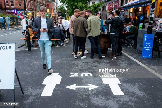 Social distancing sign is painted on the pavement as customers drink outside as bars on Hilton Street in the Northern Quarter set out tables on the...