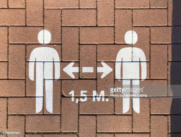 social distancing sign on pavement - social distancing stock pictures, royalty-free photos & images