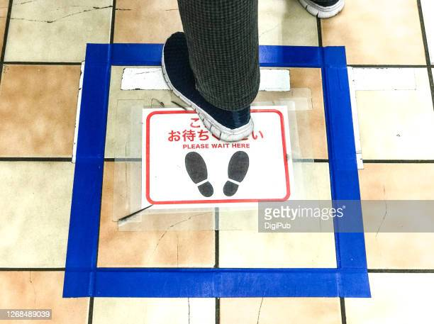 social distancing sign on the floor at a supermarket in yokohama - 説明書き ストックフォトと画像