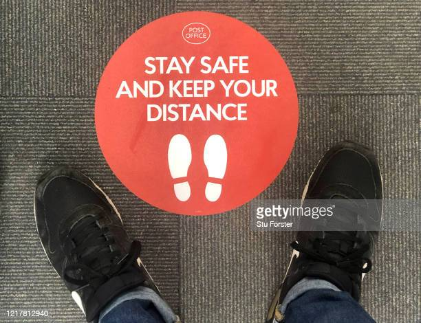 Social distancing sign on the floor of a post office on April 09, 2020 in Penarth, Wales. There have been around 60,000 reported cases of the...