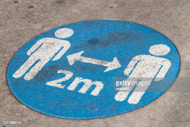 social distancing sign on the ground - sign stock pictures, royalty-free photos & images