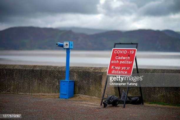 Social distancing sign sits on West Beach against the backdrop of Snowdonia on September 30, 2020 in Llandudno, United Kingdom. New local lockdown...