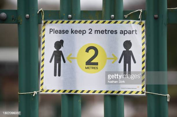 Social distancing signage is displayed onto a gate at Daven Primary School on February 14, 2021 in Congleton, England. With a surge of covid-19 cases...