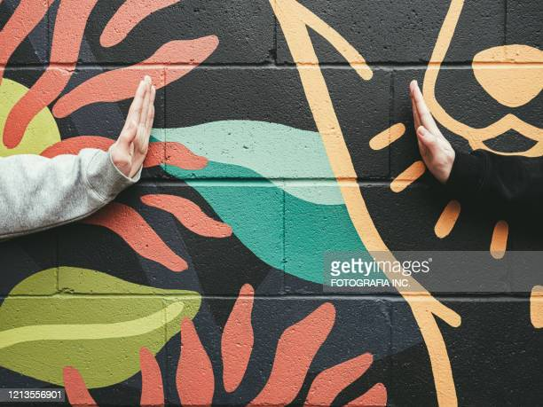 covid-19 social distancing, teenagers' hands against mural wall - street art stock pictures, royalty-free photos & images