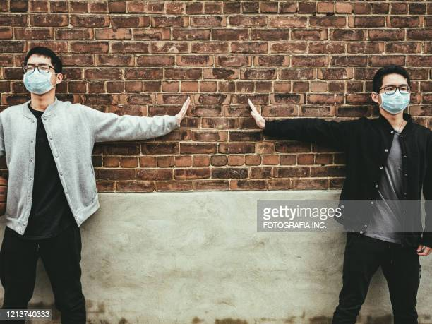 covid-19 social distancing, teenagers' hands against outdoor wall - social distancing stock pictures, royalty-free photos & images