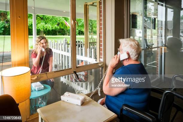 sociaal distantiëren door een venster - bezoek stockfoto's en -beelden