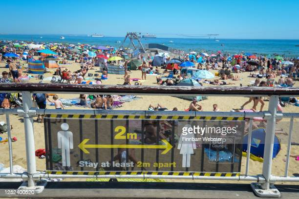 A social distancing warning sign is displayed against a backdrop of a crowded beach on June 25 2020 in Bournemouth United Kingdom The UK is...