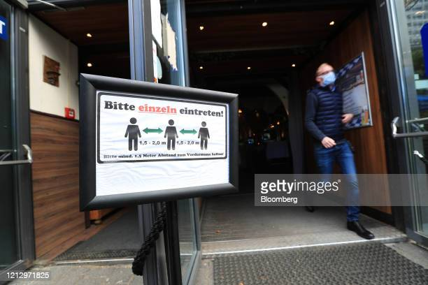 Social distancing warning sign stands on display at the entrance of a Bavarian-themed beer hall ahead of reopening in Berlin, Germany, on Thursday,...