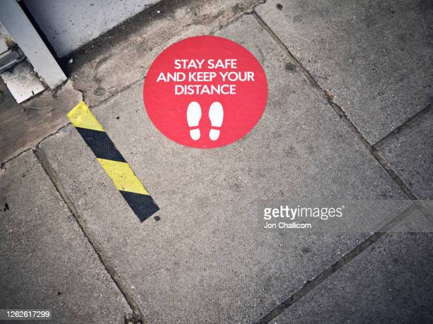 social distancing / wearing mask signs, in shopfronts on a london high street - lockdown stock pictures, royalty-free photos & images