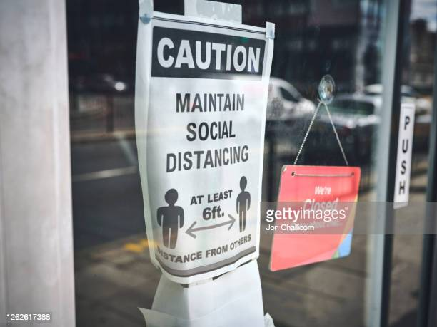 social distancing / wearing mask signs, in shopfronts on a london high street - uk stock pictures, royalty-free photos & images