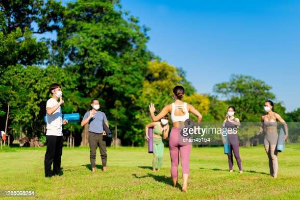 social distancing yoga class group in the open air. instructor leads yoga in the park. people exercise outdoor after stay safe at home due to covid-19 for relaxation with mask and social distancing. - medium group of people stock pictures, royalty-free photos & images
