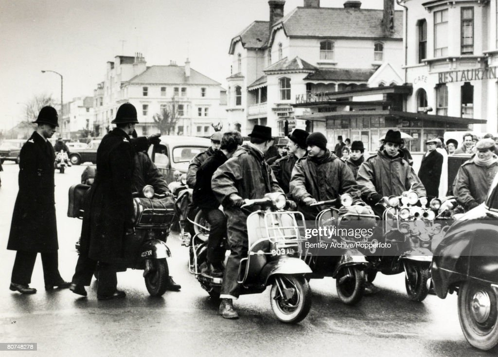 "Social History Great Britain. pic: 1964. Mods and Rockers. A group of ""Mods"" arrive on scooters in Clacton, Essex, to be closely watched by police. Seaside towns in England were the scene of running battles between ""Mods and Rockers"", young men clashing : News Photo"