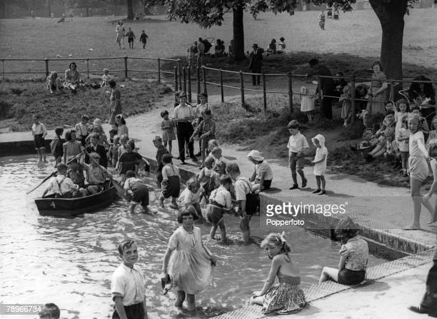 circa 1950's Northampton Northamptonshire England The boating lake at Abington Park Northampton during a heatwave with children having fun paddling...