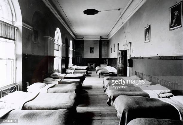 circa 1920 Doncaster Yorkshire A line of beds in the dormitory of the Balby Doncaster workhouse Photograph by Luke Bagshaw