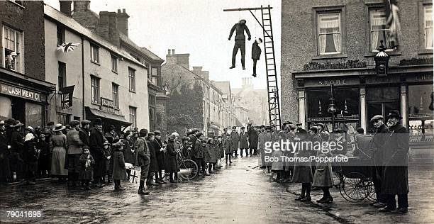 Social History World War I England Effigies of the Kaiser and Little Willie hang at Brackley Northamptonshire as a crowd gathers on Armistice Day...
