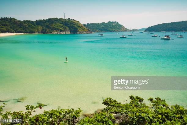 social isolation in phuket during covid-19 outbreak with panoramic aerial view of yacht on crystal clear water when sunset in nai harn beach, phuket, thailand - 360 fotografías e imágenes de stock