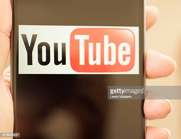 Social media Close up of mobile phone being held in a hand with the screen showing the classic icon for You Tube