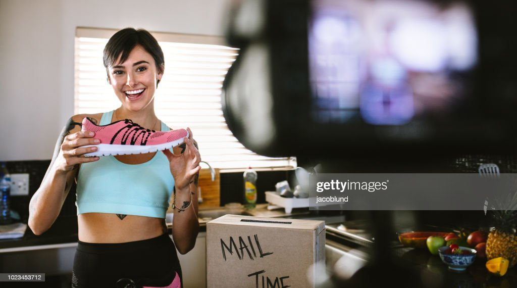 Social media influencer reviewing sports shoe : Stock Photo