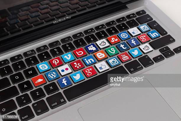 social media logos on macbook keyboard - social media icon stock photos and pictures