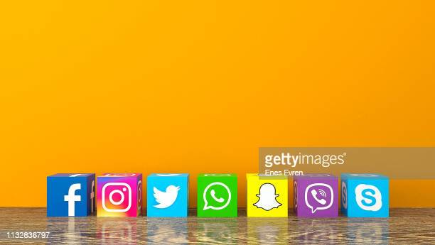 social media services icons with on wooden desk with an orange color wall - facebook stock pictures, royalty-free photos & images