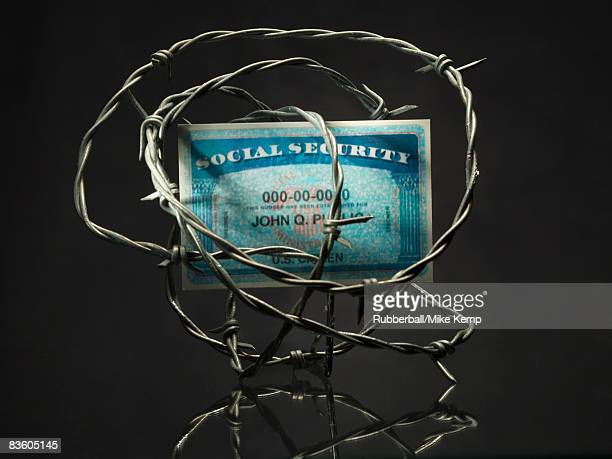 Social security card surrounded by barbed wire.