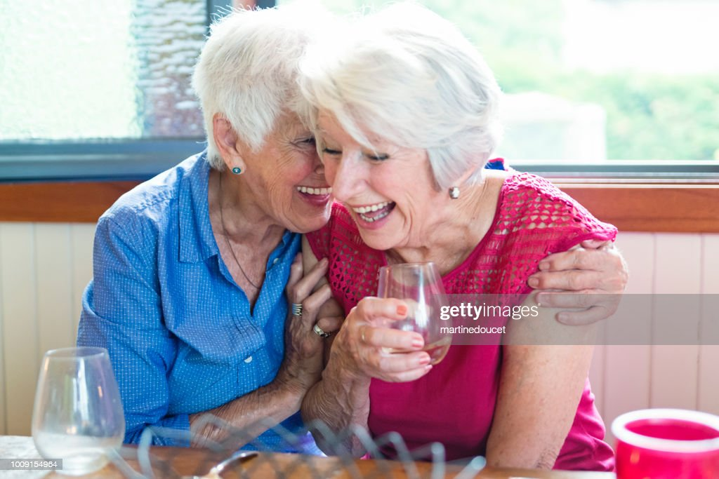 Social senior old friends laughing at dinner in summer house. : Stock Photo