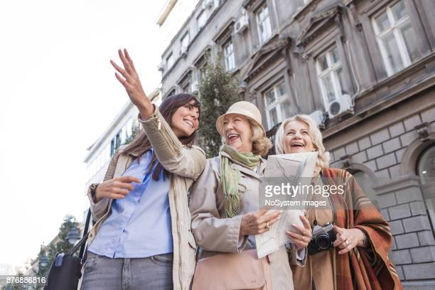social seniors. active seniors ladies traveling, exploring the city, looking at map, asking young woman, passenger for directions - tourism stock pictures, royalty-free photos & images