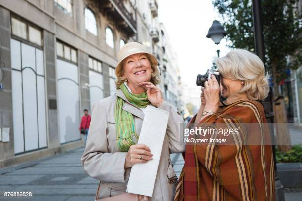 Social Seniors. Active seniors ladies traveling, exploring the city, photographing each other