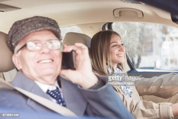 Sozialer Senioren. Großvater und Enkelin mit dem Auto fahren. Er ist Mobiltelefon verwenden.