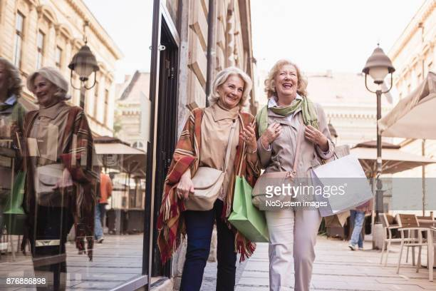 sozialer senioren. frauen in führungspositionen shoppen, spaß haben und lachen auf der straße - freundin stock-fotos und bilder