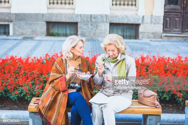 social seniors. social seniors. two senior ladies, tourist traveling, exploring the city, having a lunch break outdoors - senior lunch stock photos and pictures