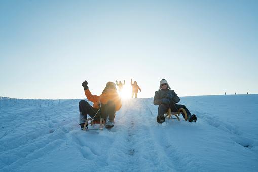 Social Seniors, tobogganing on sunny winter day 818510502